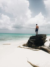 man standing on a rock on a white sand beach