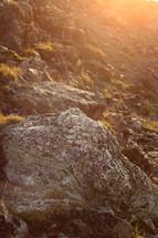 sunlight shining on rocks on a mountainside