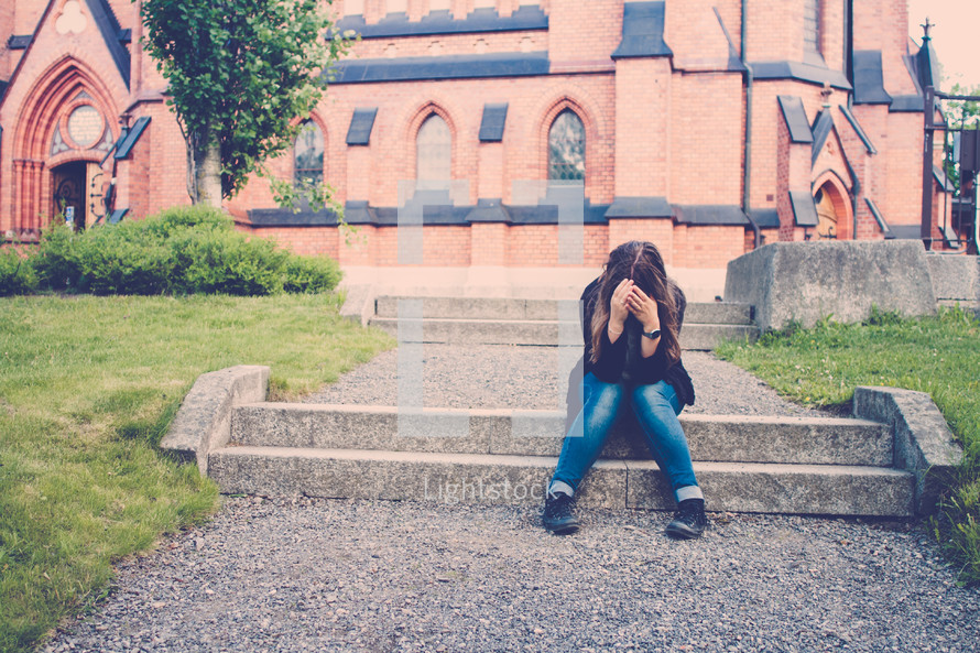 woman sitting on steps holding her head down