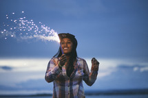A smiling woman holding a fiery sparkler.