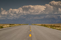 Road leading to mountains on the horizon with billowing clouds.