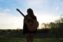 a girl standing outdoors with a guitar on her back