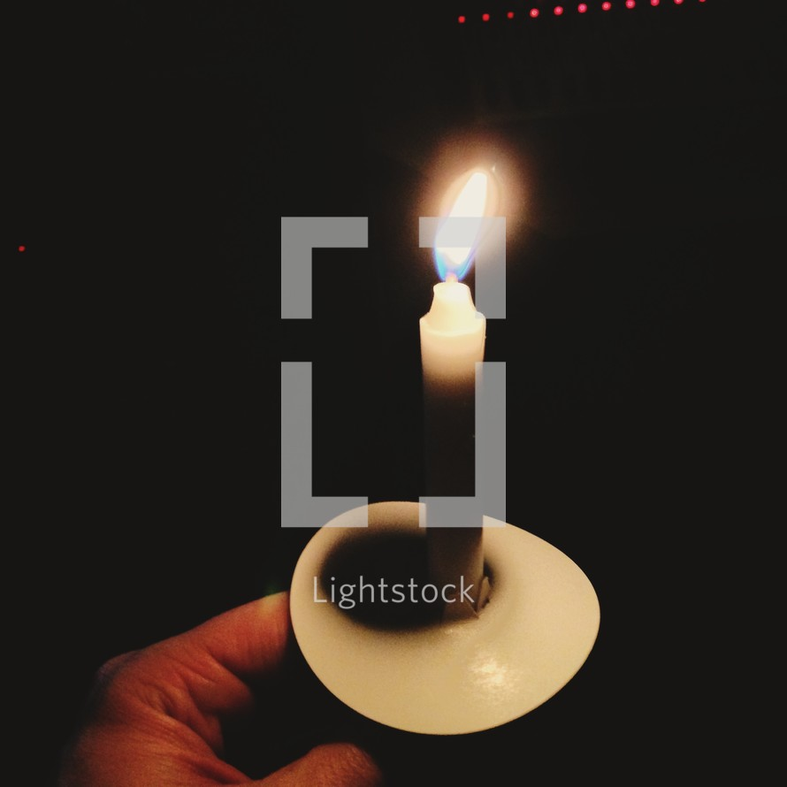 Man holding a candle at a Christmas eve service.