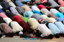 Muslim men bow in prayer at a city mosque