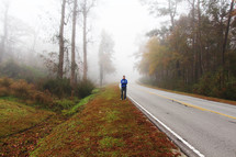 a man standing on the side of a foggy road