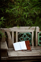 a Bible and journal on a park bench