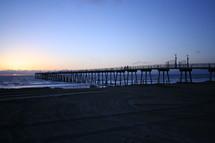 Long pier off beach into ocean at sunset.
