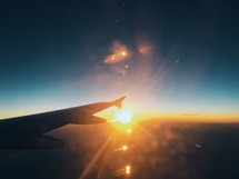 the wing of a plane in flight at sunset