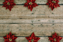 red poinsettias on wood boards