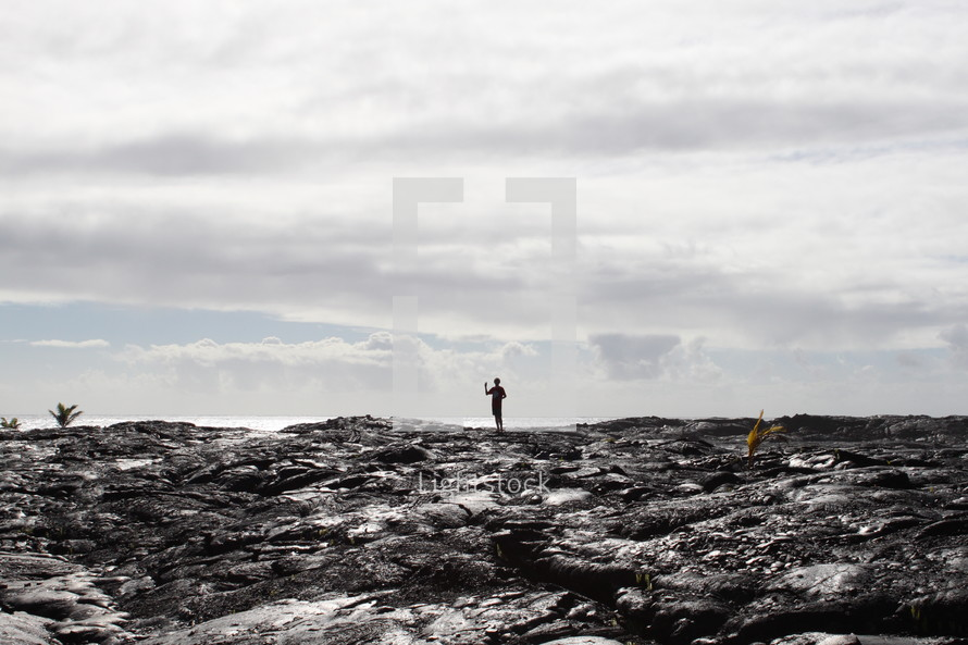 a man standing on volcanic ash