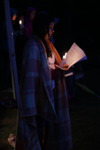a woman in a blanket holding a candle and sheet music