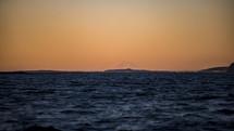 orange sky and choppy sea water
