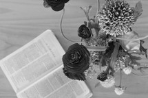 pages of an open Bible and vase of flowers