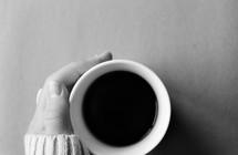 hand in a sweater on a coffee mug