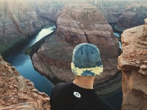 man looking down at a river in a canyon