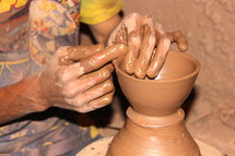 Hands molding clay on a potter's wheel.