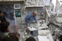 a man carving statues into stone