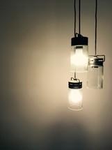 Three hanging lights lighting a brown wall.