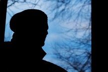 silhouette of a man in a wool cap outdoors
