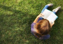 a girl reading a Book in grass