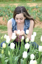 a girl smelling white tulips