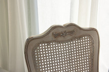 wicker back chair in a window
