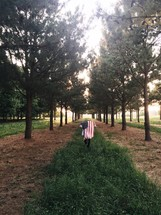 man walking with an American flag draped over his back