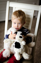 a toddler boy sitting in a chair hugging stuffed animals
