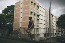 man sitting on a railing near apartments