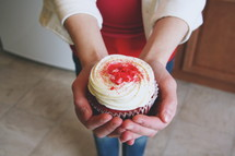 A woman holding out a cupcake.