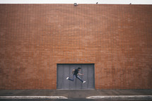 man leaping in front of a brick building