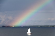 Rainbow in the sky and a sailboat on the water