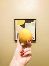 a woman holding up a lemon