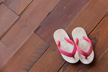 Child's flip flops on a wooden floor.