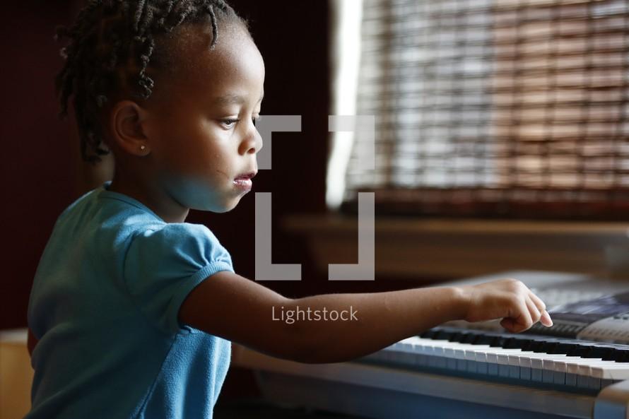 toddler girl playing a digital piano