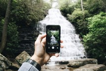 man taking a picture of a waterfall with his cellphone