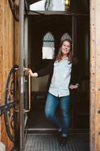 Woman standing in a doorway entrance holding the door.