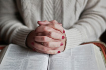 a woman praying over an opened Bible