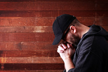 Caucasian man with his hands folded and head bowed in prayer.