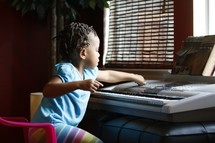 toddler girl playing a digital piano