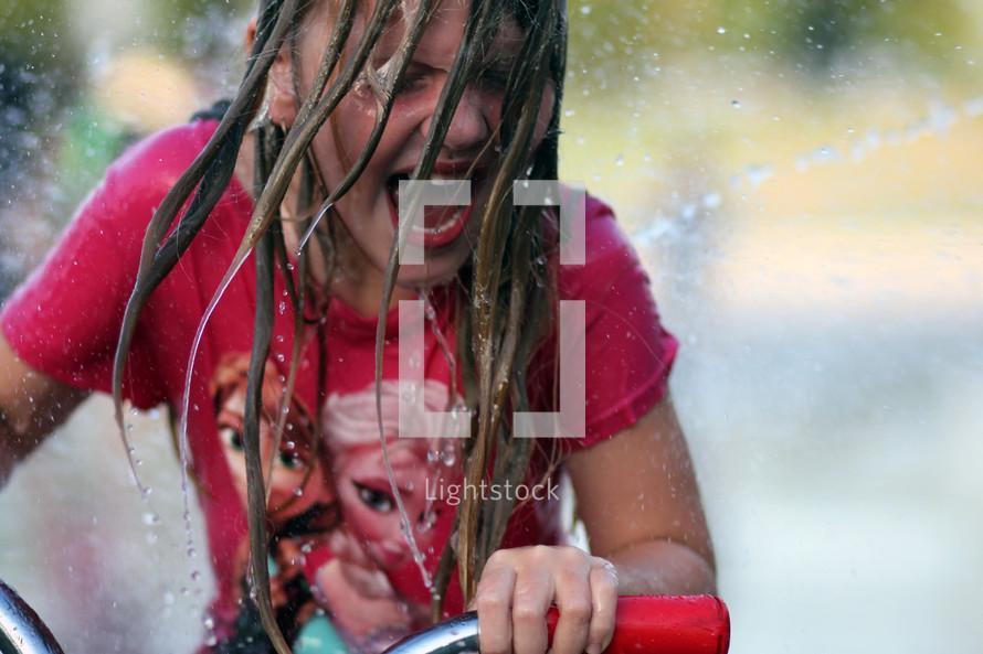 a girl child riding her bike through a sprinkler