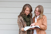 Two women looking at a Bible together.