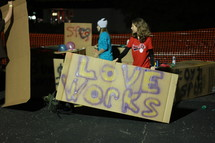 "Teens holding cardboard ""love"" signs."