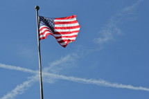 American flag on a flag pole with airplane vapor trails in the sky in the shape of a cross