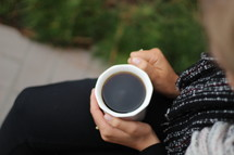 a woman holding a mug of coffee in her lap