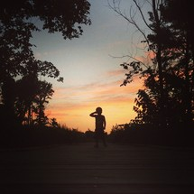 silhouette of a little boy at sunset
