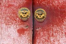 Chinese door handles on an ancient red door