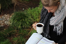 a woman reading a Bible and holding a mug