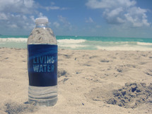 living water bottle on the sand of a beach