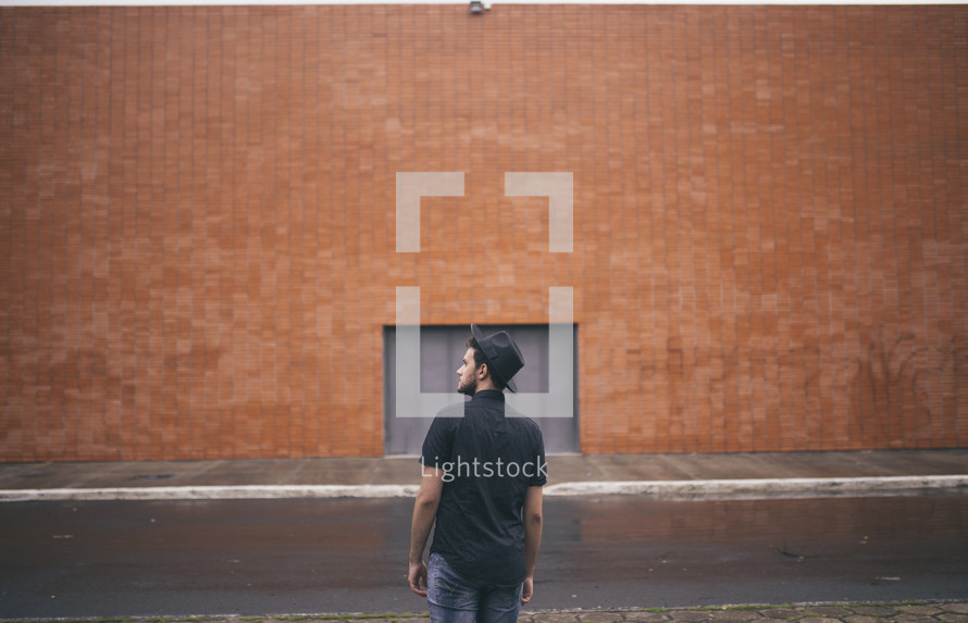 man standing with his back to the camera and a brick warehouse